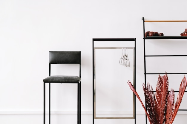 Minimaal interieurontwerp van woonkamer met kledingrek, stoel en planken.