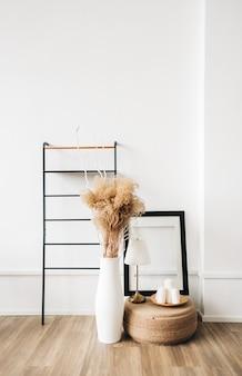 Minimaal interieurontwerp van woonkamer met planken, fotolijst en vaas met pampagras