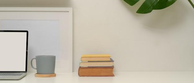 Minimaal kantoor aan huis met mock-up laptop, beker, boeken, frame, plantenhuis en kopie ruimte op witte tafel