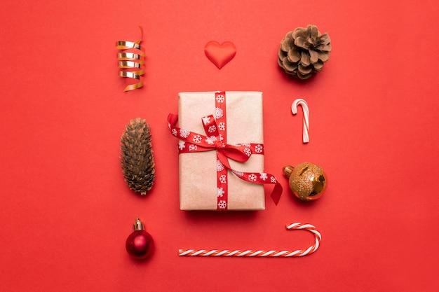 Minimaal nieuwjaarsgeschenk, gouden kerstversieringen, dennenappels op rood. plat lag, bovenaanzicht