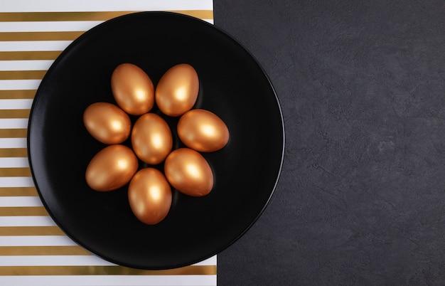 Minimaal pasen-concept. stijlvolle pasen gouden versierde eieren op zwarte plaat geïsoleerd op zwart marmeren achtergrond