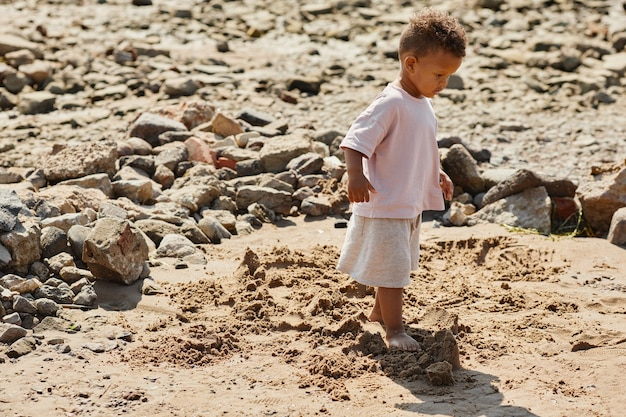 Minimaal portret van de volledige lengte van een schattige babyjongen die in het zand loopt op de kopieerruimte van het strand