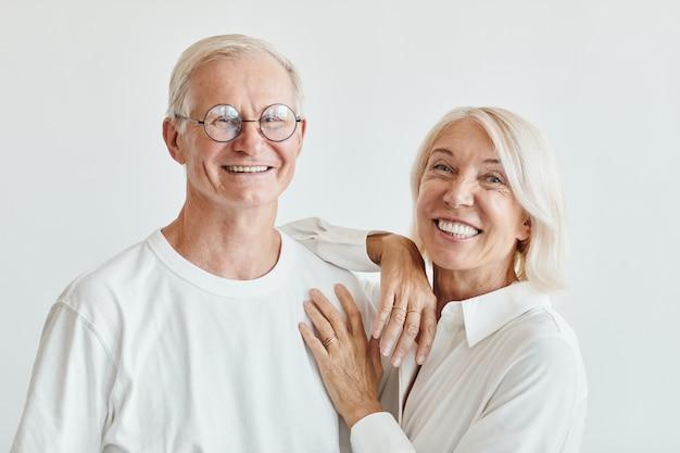 Minimaal portret van een modern senior koppel dat wit draagt tegen een witte achtergrond en glimlacht naar de camera