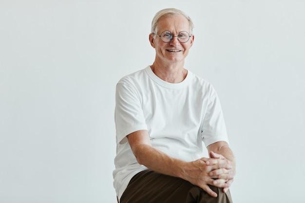 Minimaal portret van lachende senior man die naar de camera kijkt terwijl hij tegen een witte achtergrond poseert, kopieer ruimte