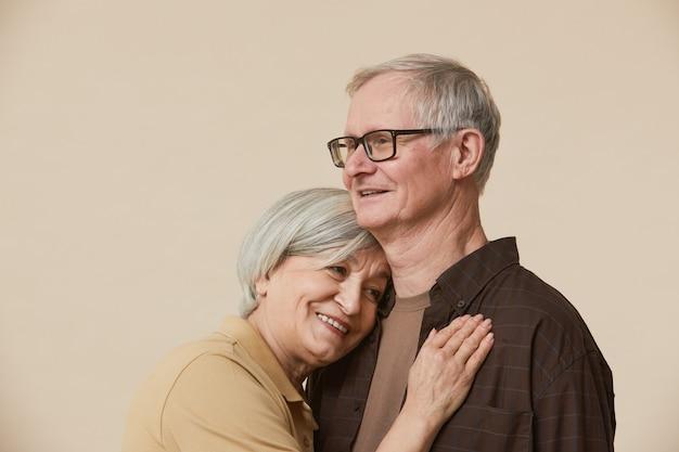Minimaal portret van liefhebbend senior paar omarmen tegen beige achtergrond, kopieer ruimte