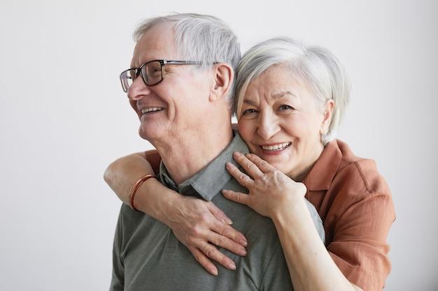 Minimaal portret van zorgeloos senior koppel omarmen en kijkend naar de camera terwijl ze tegen een witte achtergrond staan