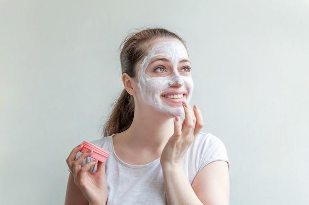 Minimaal schoonheidsportret jong vrouwenmeisjesportret die wit voedend masker of room op gezicht toepassen dat op witte muur wordt geïsoleerd. huidverzorging reinigende eco organische cosmetische spa concept.
