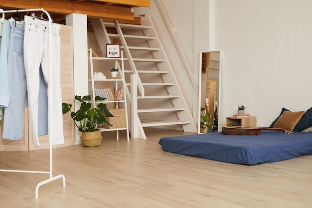 Minimaal slaapkamerinterieur met laag bed en houten vloeren