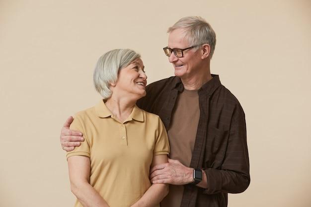 Minimaal taille-up portret van zorgeloos senior paar omarmen en kijken naar elkaar terwijl ze tegen een beige achtergrond staan
