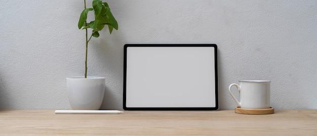 Minimaal thuiskantoor met mock-up tablet, koffiekopje en plantenpot op houten bureau