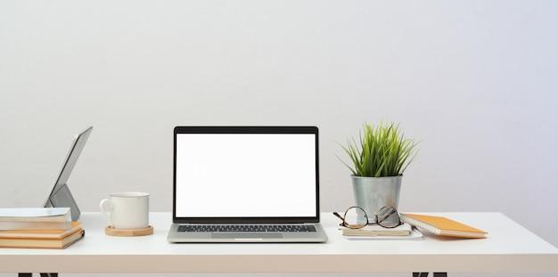 Minimaal thuiskantoor met open lege laptopcomputer en kantoorbenodigdheden