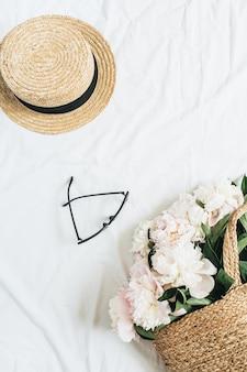 Minimaal vrouwelijk oppervlak met strooien hoed, bril, witte pioenrozen boeket in zak