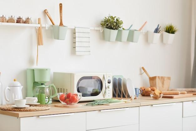Minimaal wit keukeninterieur met houten accenten in klein en gezellig appartement