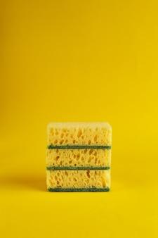 Minimale achtergrond met gele sponzen voor de afwas. trendy gele achtergrond