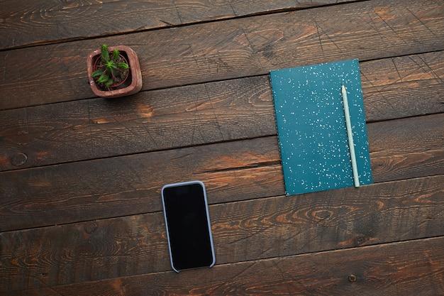 Minimale achtergrondafbeelding van smartphone en planner op gestructureerd houten bureau, bovenaanzicht,
