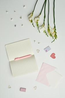 Minimale achtergrondsamenstelling van lege planner en schattig briefpapier tegen terwijl tafelachtergrond met bloemendecor,