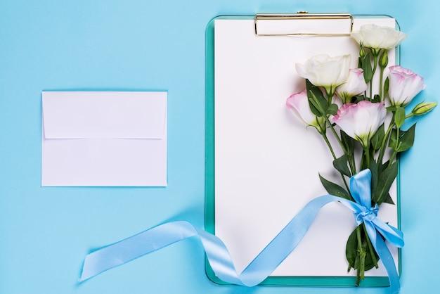 Minimale compositie met een eustoma bloemen in een envelop met klembord op een blauwe achtergrond, bovenaanzicht. valentijnsdag, verjaardag, moeder of bruiloft wenskaart