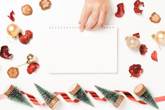 Minimale creatieve platte lay van winterkerst traditionele compositie en nieuwjaar. bovenaanzicht open mockup zwarte notebook voor tekst op witte achtergrond kopie ruimte.