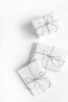 Minimale feestelijke vakantiesamenstelling voor kerstmis of nieuwjaar. drie geschenken verpakt in wit papier op witte tafel. plat lag, bovenaanzicht.
