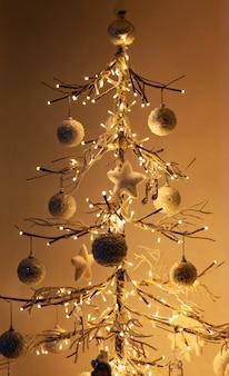Minimale kerstboom staan voor witte muur met warm licht en schaduwen