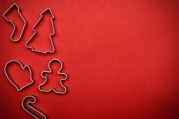 Minimale kerstmisachtergrond met de vormen van het kerstmisbaksel op rode achtergrond