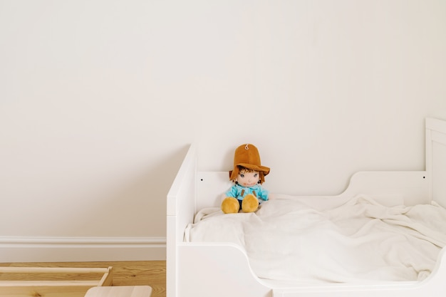 Minimale kinderkamer voor peuter in witte en houten kleuren. minder verspilde levensstijl bij opvoeding
