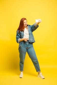 Minimale kleding nodig voor selfie. blanke vrouw portret op gele ruimte