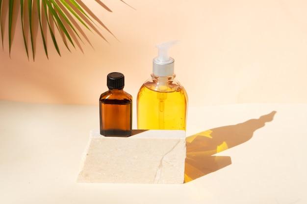 Minimale moderne cosmetische producten worden weergegeven met twee etherische olieflessen op een beige achtergrond met schaduwoverlay