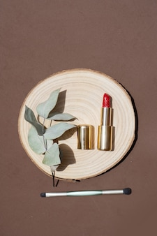 Minimale moderne cosmetische scène met make-upborstel, lippenstift en palmschaduwoverlay