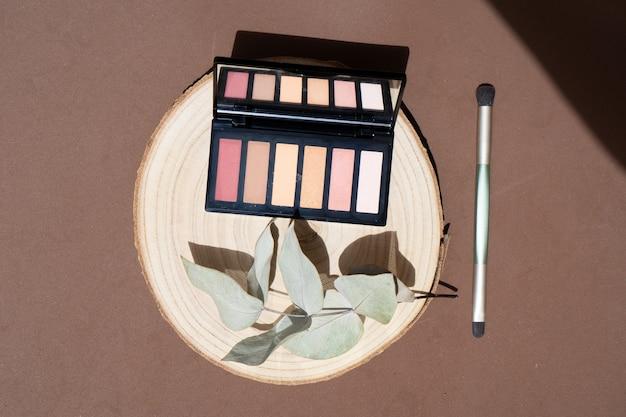 Minimale moderne cosmetische scène met make-upborstel, oogschaduw en eucaliptusbladeren