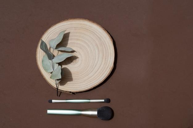 Minimale moderne cosmetische scène met make-upborstels en eucaliptusbladeren