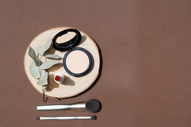 Minimale moderne cosmetische scène met make-upborstels, poeder en eucaliptusbladeren