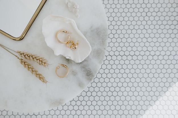Minimale modesamenstelling met gouden oorbellen in zeeschelp op marmeren tafel met spiegel en tarwestelen