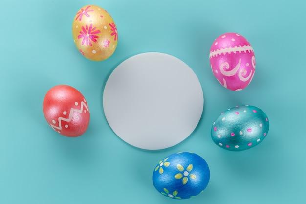 Minimale paaskaart. vijf trendy kleur van pasen versierde eieren op lichtblauw