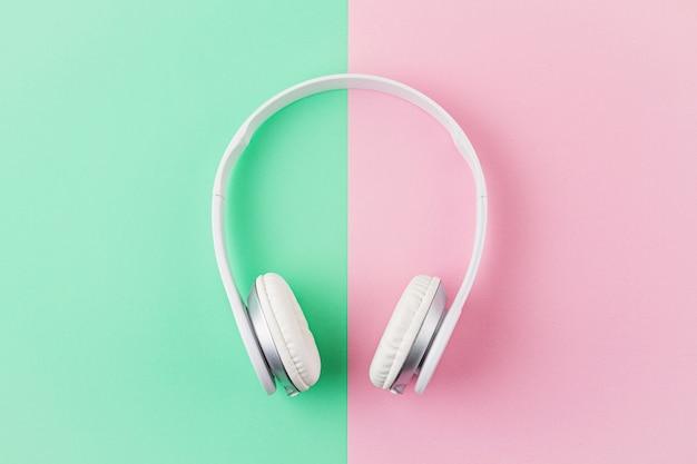 Minimale plat lag met draadloze koptelefoon op roze en lichte mint achtergrond.