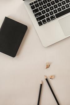 Minimale plat leggen, bovenaanzicht levensstijlsamenstelling met laptop, potloden, notitieboekje op neutraal pastelbeige.