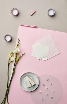 Minimale samenstelling van brief in envelop over roze grafische achtergrond met bloemendecor,