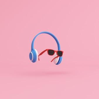Minimale scène van zonnebril en hoofdtelefoon op roze achtergrond, muziekconcept.