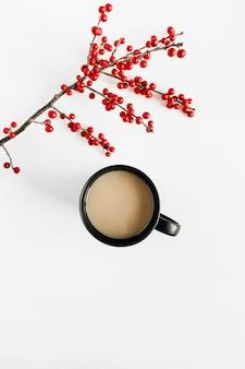 Minimale seizoenssamenstelling. zwarte kopje koffie met tak van rode bessen op witte tafel. plat lag, bovenaanzicht.