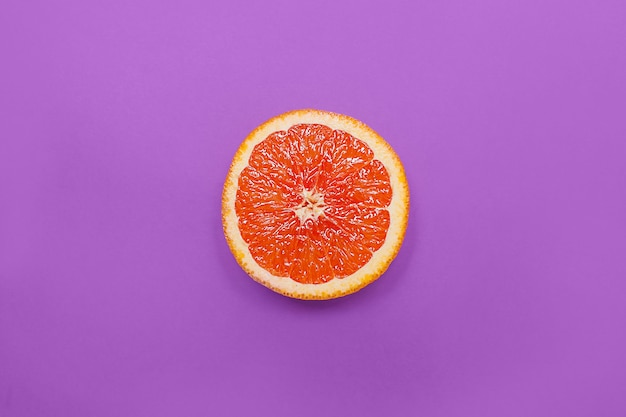 Minimale stijl, creatieve lay-outsinaasappel en grapefruit op purpere achtergrond