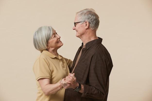 Minimale taille portret van gelukkig senior paar dansen en kijken naar elkaar tegen beige achtergrond