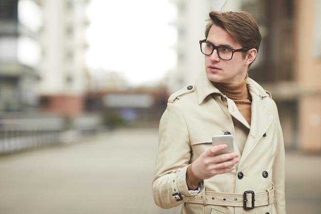 Minimale taille portret van moderne jonge zakenman trenchcoat dragen en houden smartphone wegkijken terwijl poseren vol vertrouwen in de stedelijke omgeving, kopie ruimte