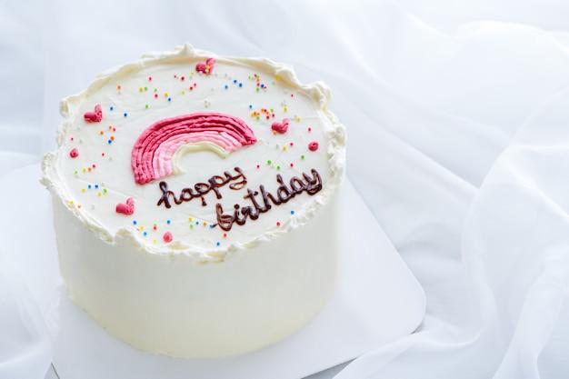 Minimale verjaardagstaart en versierde regenboog bovenop met witte doekachtergrond. thais dessert