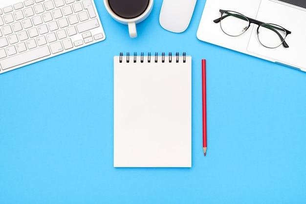 Minimale werkplek met laptop en blanco notitieblok