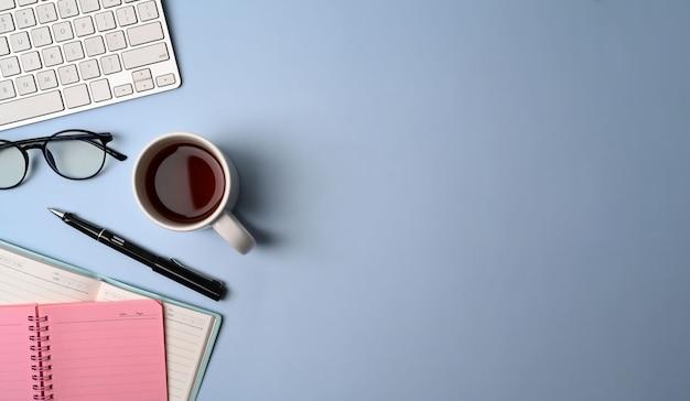 Minimale werkplek met notebook, bril, koffiekopje, toetsenbord en pen op blauwe achtergrond.