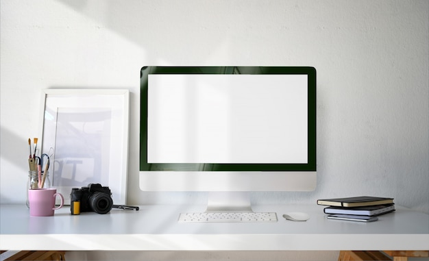 Minimale werkruimte desktop computer leeg scherm, poster en benodigdheden