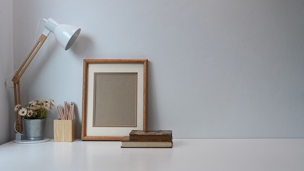 Minimale werkruimte met frame, potloden, koffiekopje, lamp en oud boek op witte tafel.