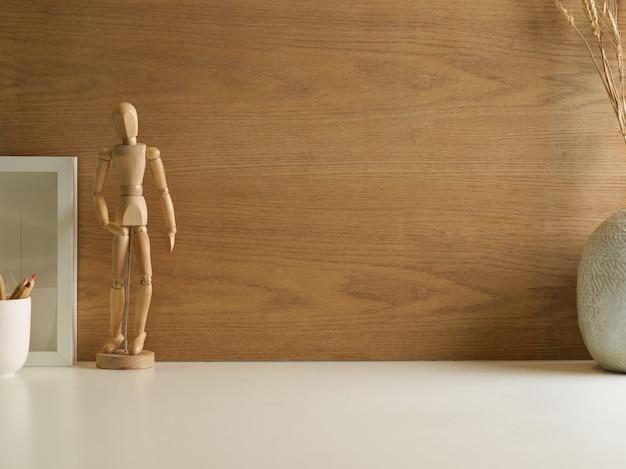 Minimale werkruimte met houten figuur, andere decoraties en kopie ruimte met houten muur achtergrond