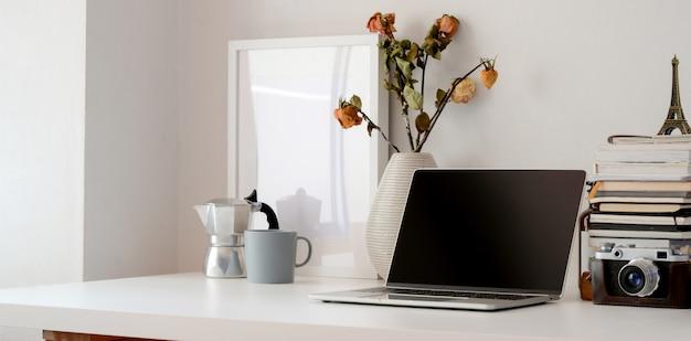 Minimale werkruimte met laptop, camera, kantoorbenodigdheden en vaas met droge rozen