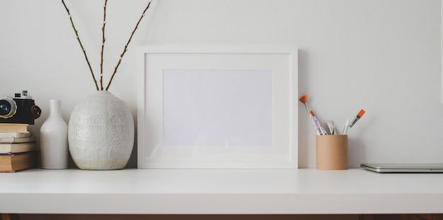 Minimale werkruimte met lege fotolijst en kantoorbenodigdheden op witte houten tafel en witte muur